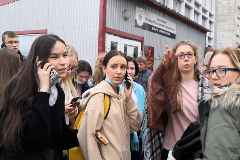 In this grab taken from video, a group of students react and speak on their phones near the...
