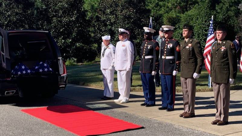 An honor guard waits to escort the cremated remains of six Alabama veterans and one qualifying...
