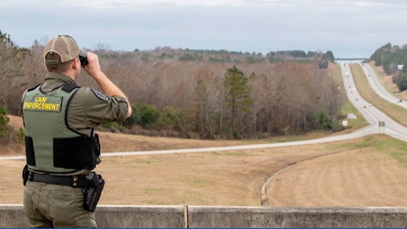Alabama conservation officers watch to stop vehicles bringing in deer carcasses.