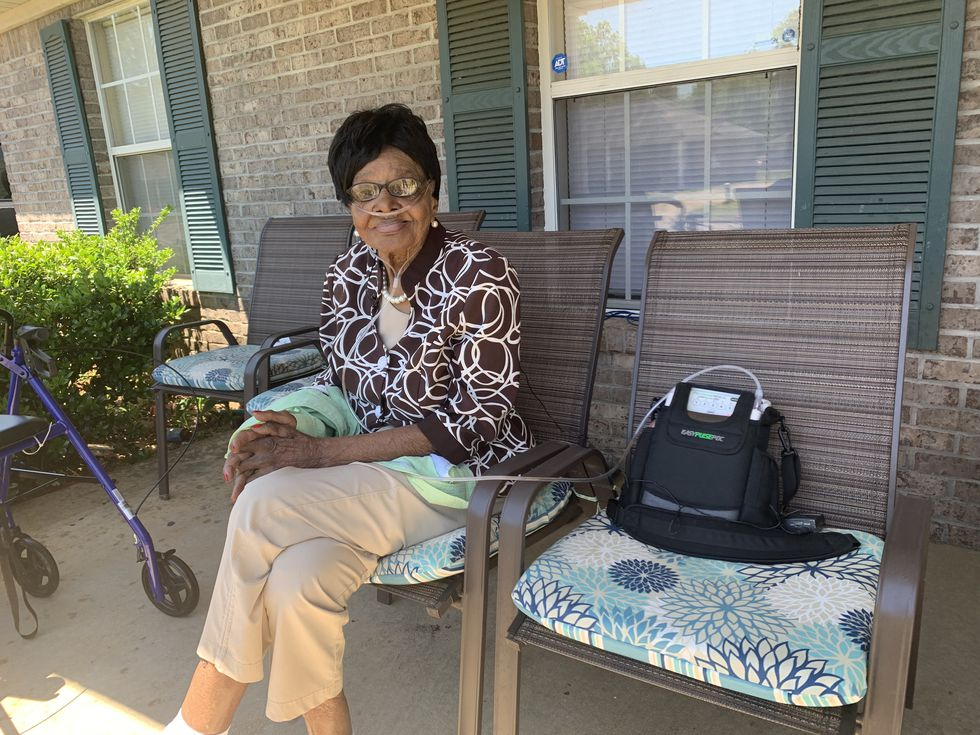 Mrs. Georgia Sankey sits on her front porch, awaiting the arrival of friends and family.