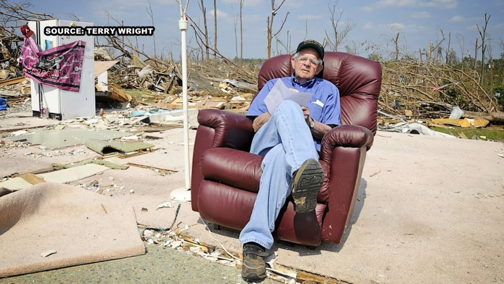 Man sits in recliner where home used to stand.