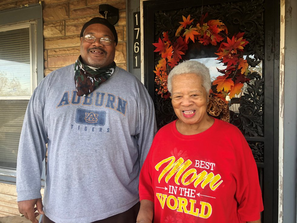 Mrs. Dianne Hasberry and Reginald Hasberry smile happily after receiving Thanksgiving meal from...