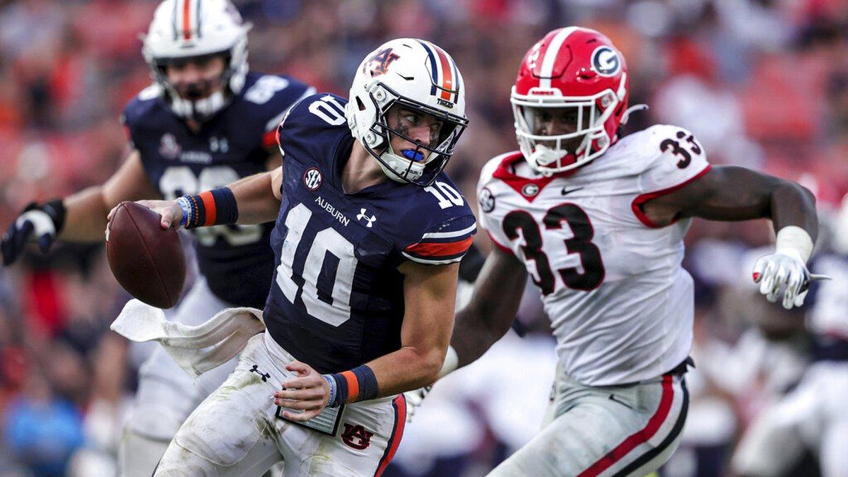 Auburn quarterback Bo Nix (10) tries to elude the pressure from Georgia linebacker Robert Beal...