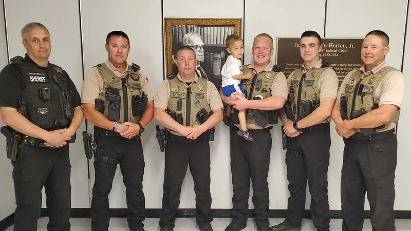 Morgan County Deputies with their young friend almost one year later