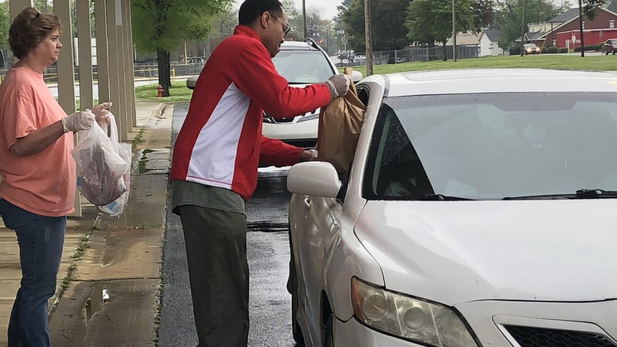Teachers from Tuscaloosa's Central High School give food to families in a curb-side pick up...