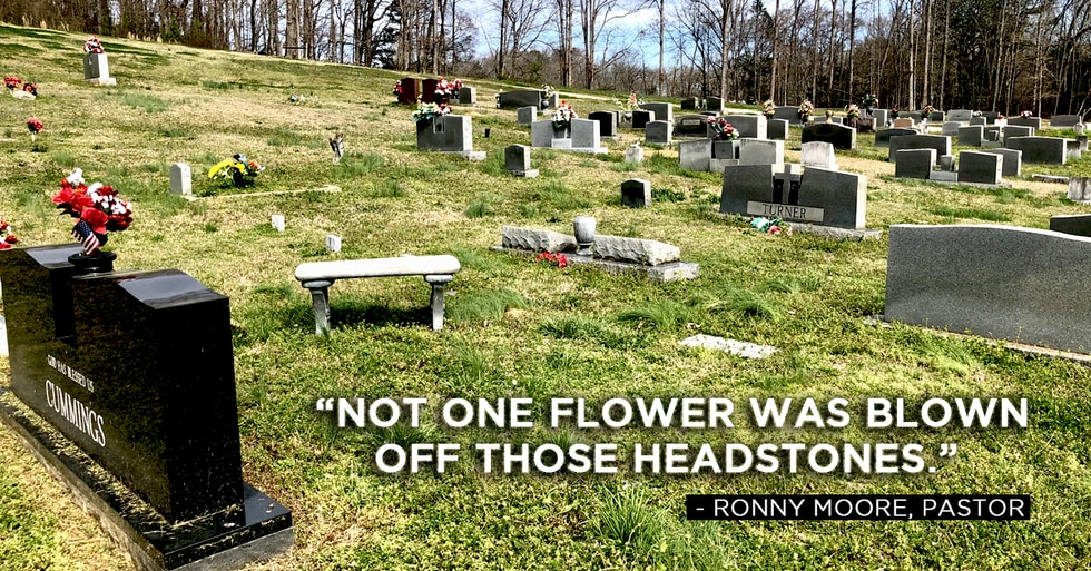 """""""Not one flower was blown off those headstones,"""" Moore said. The cemetery adjacent to the..."""